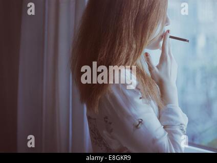 woman standing by window smoking - Stock Photo