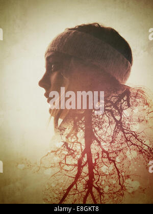 Digital composite of woman and tree - Stock Photo