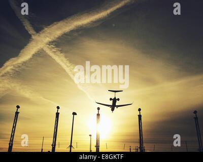 Silhouette of landing airplane - Stock Photo