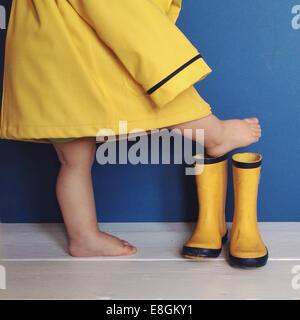 Boy in raincoat putting on wellington boots - Stock Photo