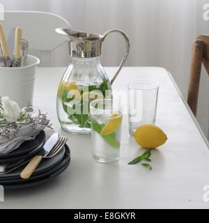 Jug and glass of water infused with fresh lemon and mint - Stock Photo