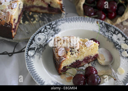 Cherry almond cake topped with almonds and fresh cherries - Stock Photo