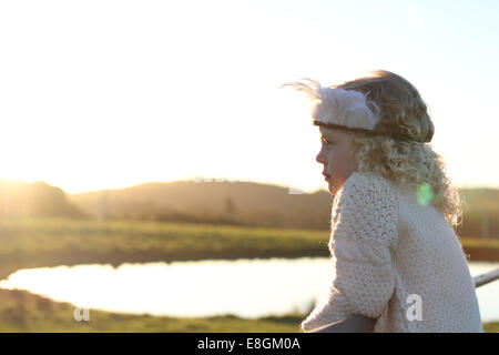 Girl wearing feather headdress looking at lake - Stock Photo