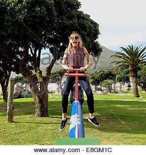Woman on seesaw in park - Stock Photo
