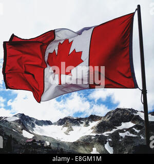 Canada, Whister, Flag of Canada waving over mountains - Stock Photo