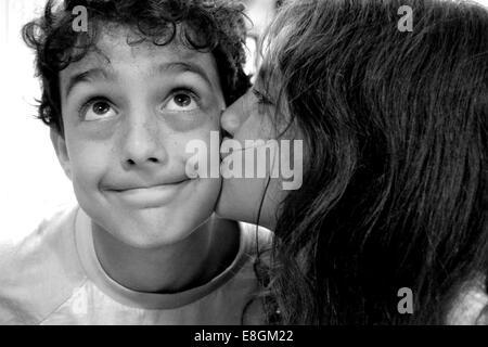 Girl kissing boy on the cheek - Stock Photo