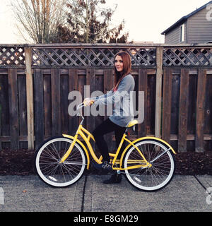 USA, Oregon, Multnomah County, Portland, Portrait of young woman riding bike - Stock Photo