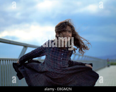 Girl spinning around holding hem of her dress - Stock Photo