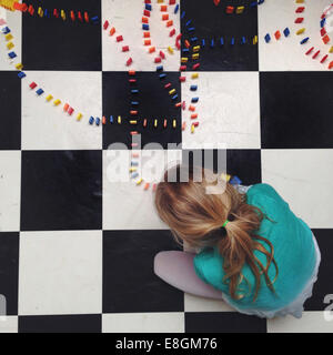 Girl (12-13) girl setting up lines of dominos - Stock Photo