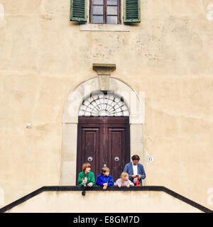 Italy, Florence, Father with three kids (10-11, 12-13) standing in front of building - Stock Photo