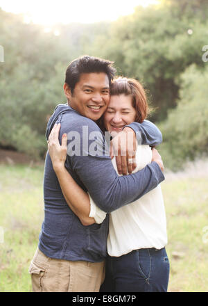 Portrait of a mid adult Couple hugging - Stock Photo
