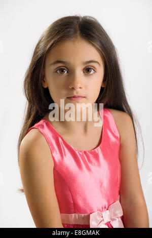 Pretty little girl in a stylish pink dress and sash looking at the camera with a solemn expression and big dark - Stock Photo