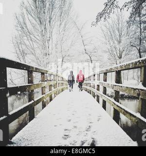 Rear view of two children walking across footbridge in the snow - Stock Photo