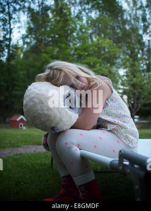 Sweden, Girl (6-7) hugging teddy bear in backyard