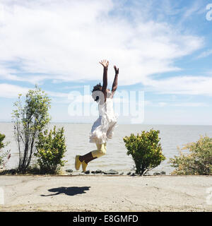 Girl jumping in air on beach - Stock Photo