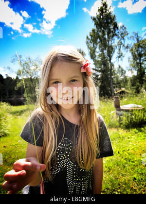 Young girl (8-9) smiling and holding straw in her hand - Stock Photo