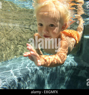 Boy swimming underwater in swimming pool - Stock Photo