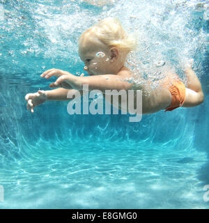 Boy swimming underwater - Stock Photo