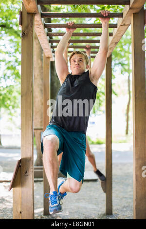 Full length of determined man hanging on monkey bars at outdoor gym - Stock Photo