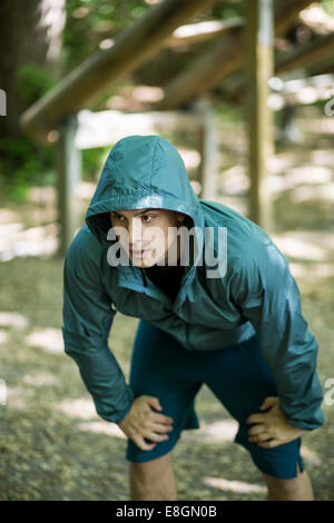 Tired man standing with hands on knees at outdoor gym - Stock Photo