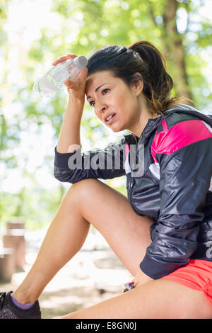 Tired woman holding water bottle after workout at park - Stock Photo