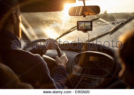 Cropped image of man driving car while using GPS by daughter - Stock Photo