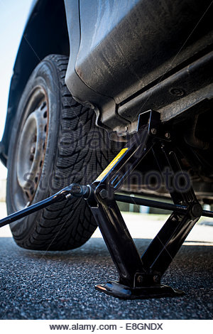 Hydraulic jack lifting car on street - Stock Photo