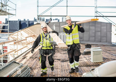 Construction workers carrying wooden planks at site - Stock Photo
