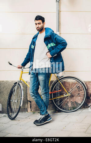 Full length portrait of confident man standing with bicycle on sidewalk - Stock Photo