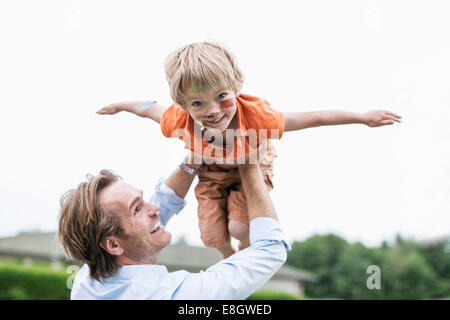 Playful father lifting injured son against clear sky - Stock Photo