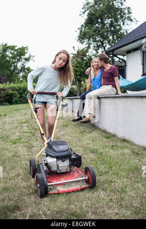 Girl mowing lawn with parents sitting in background at yard - Stock Photo
