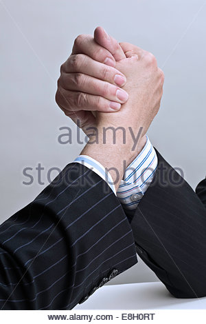 Close up of wo businessmen hand wrestling - Stock Photo