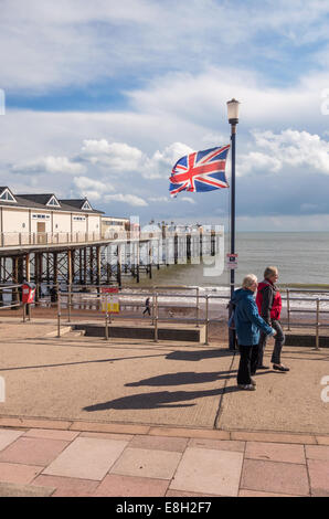 The pier stretching out to sea at Teignmouth in Devon with a union jack fluttering in the foreground. Two women - Stock Photo