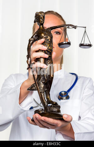 Doctor holding Lady Justice figurine - Stock Photo