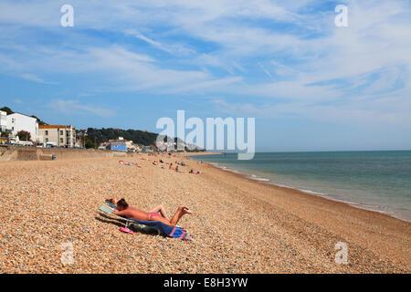Two women sunbathing on shingle beach at Sandgate Esplande Folkestone. - Stock Photo