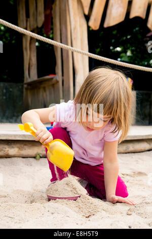 Little girl on playground balancing in sandbox - Stock Photo