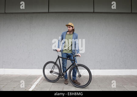 Germany, Bavaria, Munich, young man wearing basecap standing in front of a wall with his racing cycle - Stock Photo