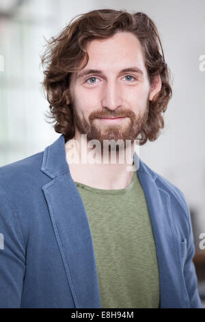 Portrait of smiling young man wearing full beard - Stock Photo