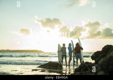 Three teenagers standing on the beach with their surfboards looking at horizon - Stock Photo