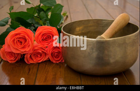 Singing bowl on wooden surface near the roses - Stock Photo