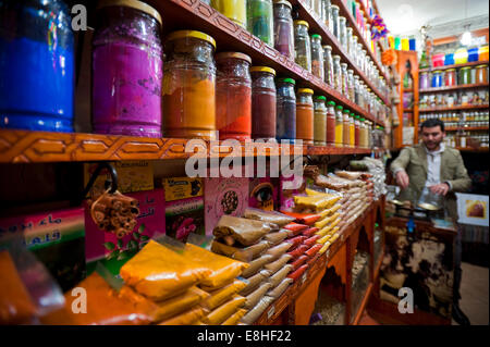 Horizontal portrait of a shop owner weighing spices in the souks of Marrakech.
