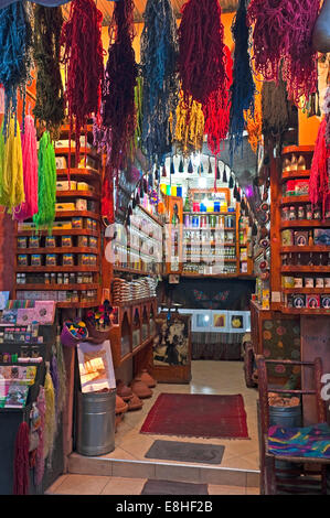 Vertical view of the colourful skeins of wool hanging outside a shop in the souks of Marrakech.
