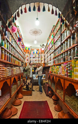 Vertical portrait of a Western tourist being served in a spice shop in the souks of Marrakech. - Stock Photo