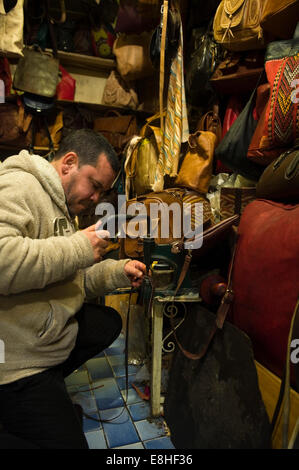 Vertical portrait of a leatherworker punching holes in a strap in a leather shop in the souks of Marrakech. - Stock Photo