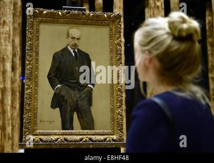 Berlin, Germany. 7th Oct, 2014. A visitor looks at the self portrait 'Stehend in Dreiviertelfigur, beide Haende - Stock Photo
