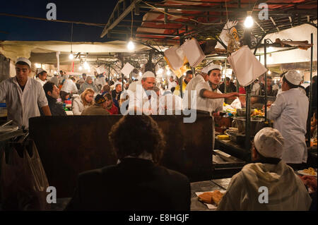 Horizontal view of a busy cooking station at a food stall in Place Jemaa el Fna (Djemaa el Fnaa) in Marrakech at - Stock Photo