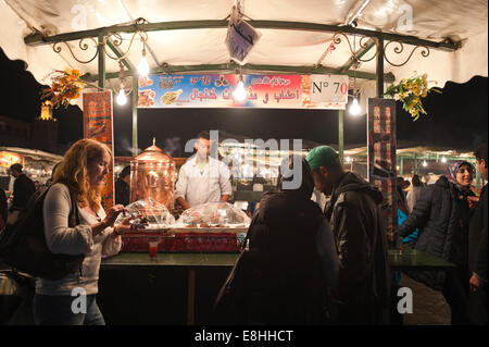 Horizontal portrait of a female tourist eating traditional food at a stall in Place Jemaa el Fna (Djemaa el Fnaa) - Stock Photo