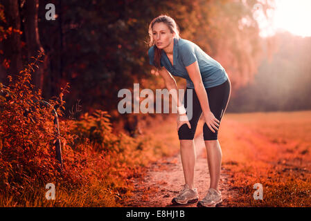 Young athletic woman taking a break from training standing resting her hands on her knees on a rural track through - Stock Photo