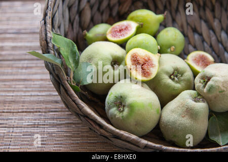 quinces and figs in woven basket with cut figs on top - Stock Photo