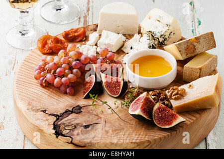 Cheese plate Assortment of various types of cheese on wooden cutting board - Stock Photo
